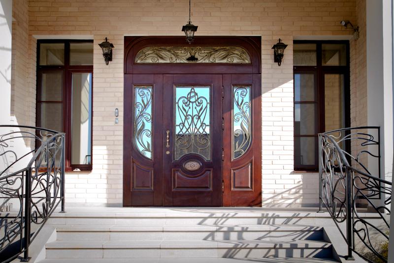 парадные двери со стеклом и элементами ковки
